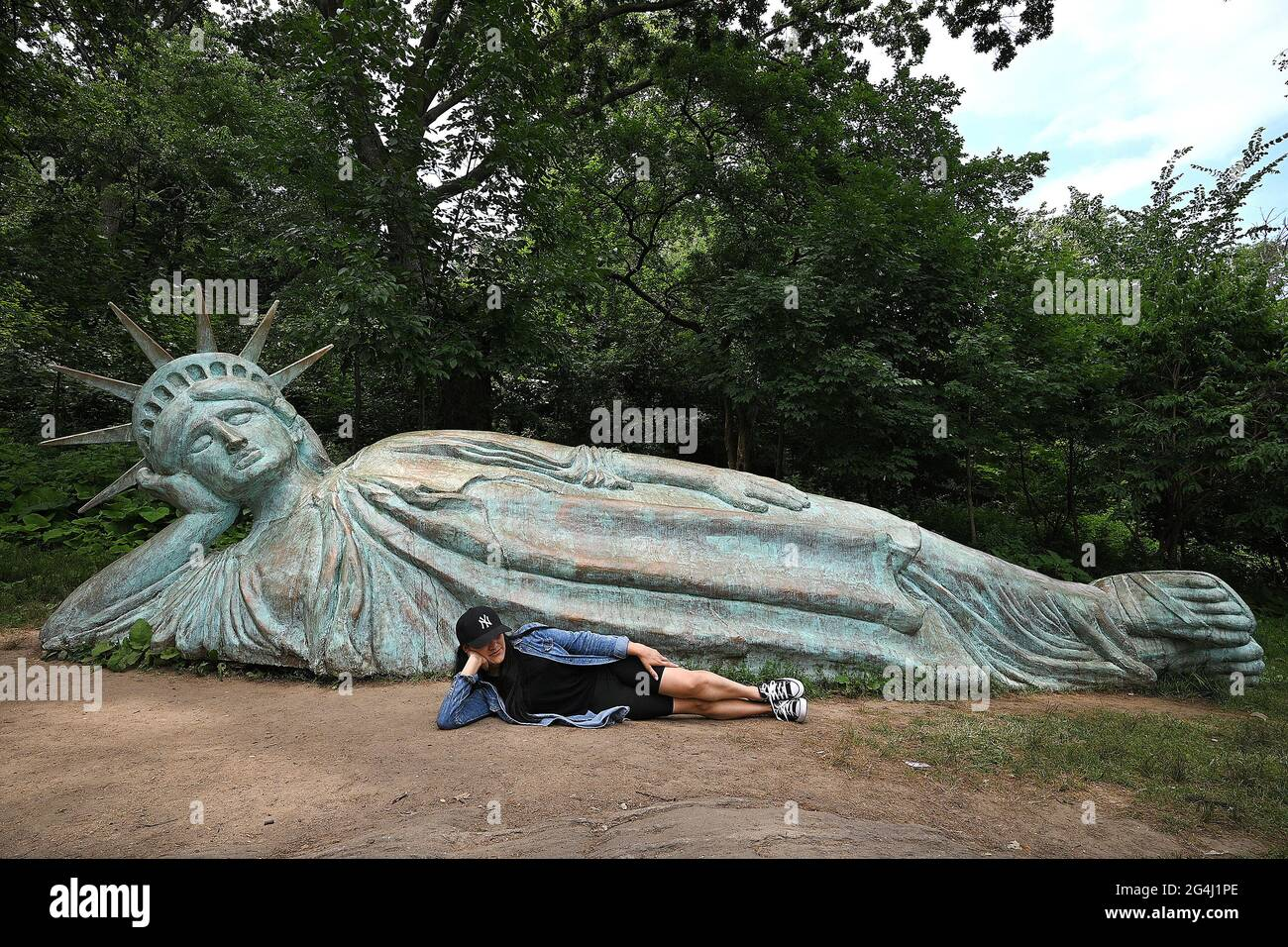"""Nueva York, Estados Unidos. 21st de junio de 2021. Iveth Manjarrez adopta la misma postura que """"Reclining Liberty"""" para unas fotos delante de la réplica de la Estatua de la Libertad de 25 pies de largo esculpida por el artista Zaq Landsberg, en Morningside Park, en Nueva York, NY, 21 de junio, 2021. (Foto de Anthony Behar/Sipa USA) Crédito: SIPA USA/Alamy Live News Foto de stock"""