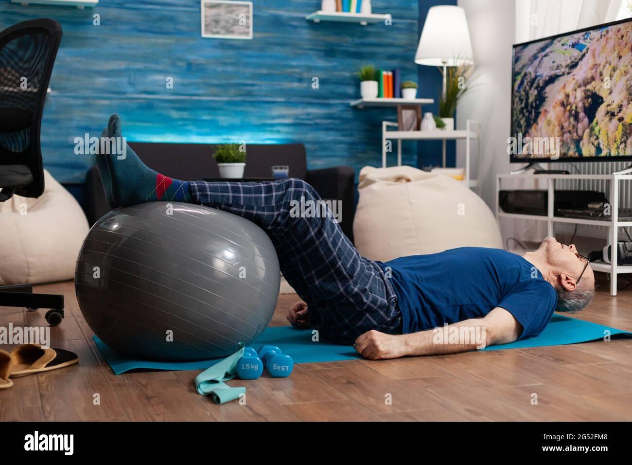 Jubilado hombre mayor haciendo bienestar calentar piernas con pelota suiza sentado en colchoneta de yoga en la sala de estar. Jubilado pensionista que practica ejercicios abdominales trabajando en la salud muscular del cuerpo Foto de stock