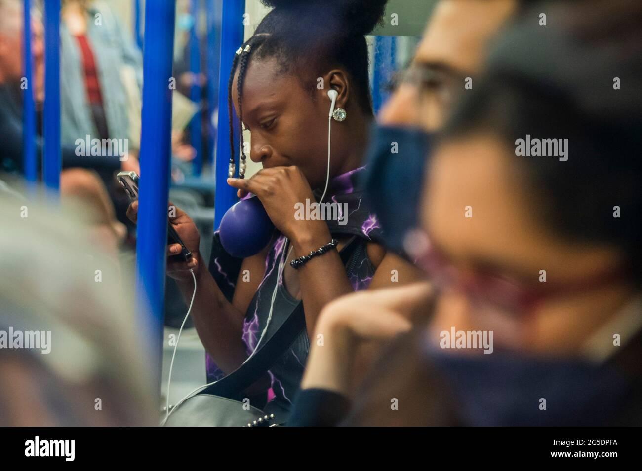 Londres, Reino Unido. 26th de junio de 2021. Una mujer negra desenmascarada se filma y chupa un balón (presumiblemente lleno de óxido nitroso) - el metro está ocupado y muchas personas no usan máscaras ya que nos acercamos al final de las restricciones del coronavirus. Crédito: Guy Bell/Alamy Live News Foto de stock