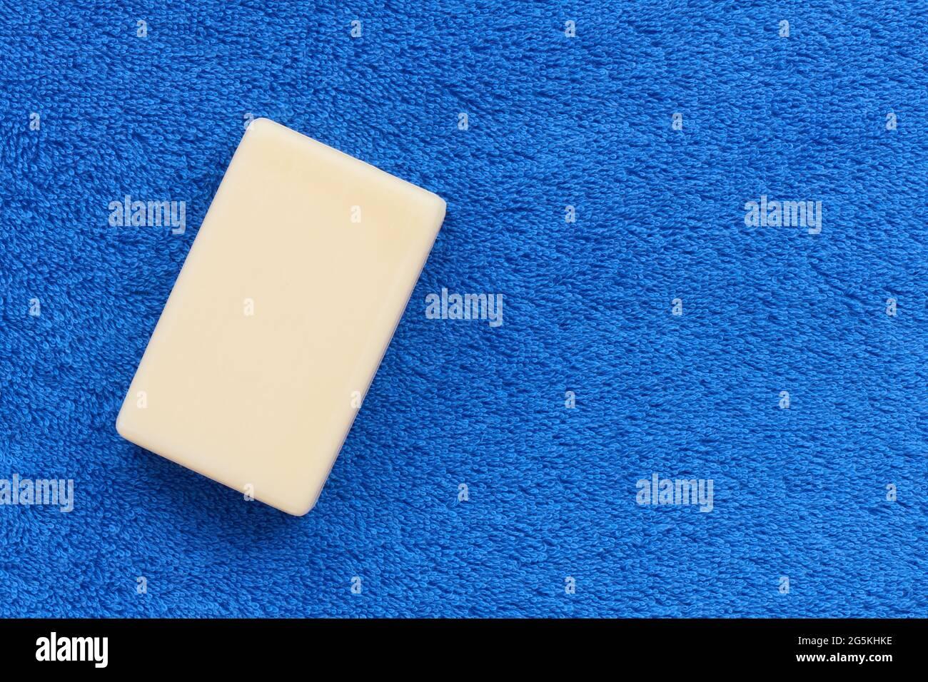 Barra blanca de jabón sobre suave toalla rústica azul con espacio de copia, concepto de higiene Foto de stock