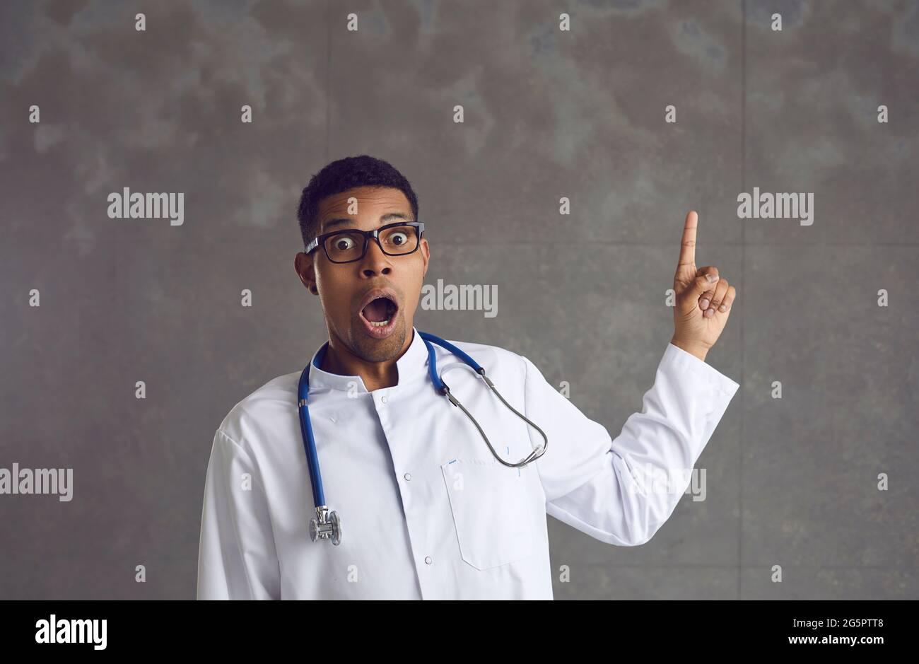 Un médico afroamericano conmocionado que apunta más fino arriba retrato del estudio de la cabeza Foto de stock