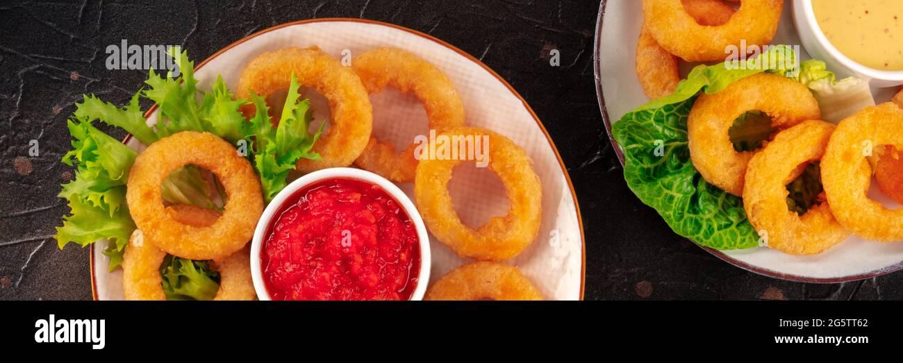 Panorama de los anillos de calamares. Anillos de calamares fritos profundos con ensalada verde y varias salsas, la parte superior plana se disparó sobre un fondo oscuro Foto de stock