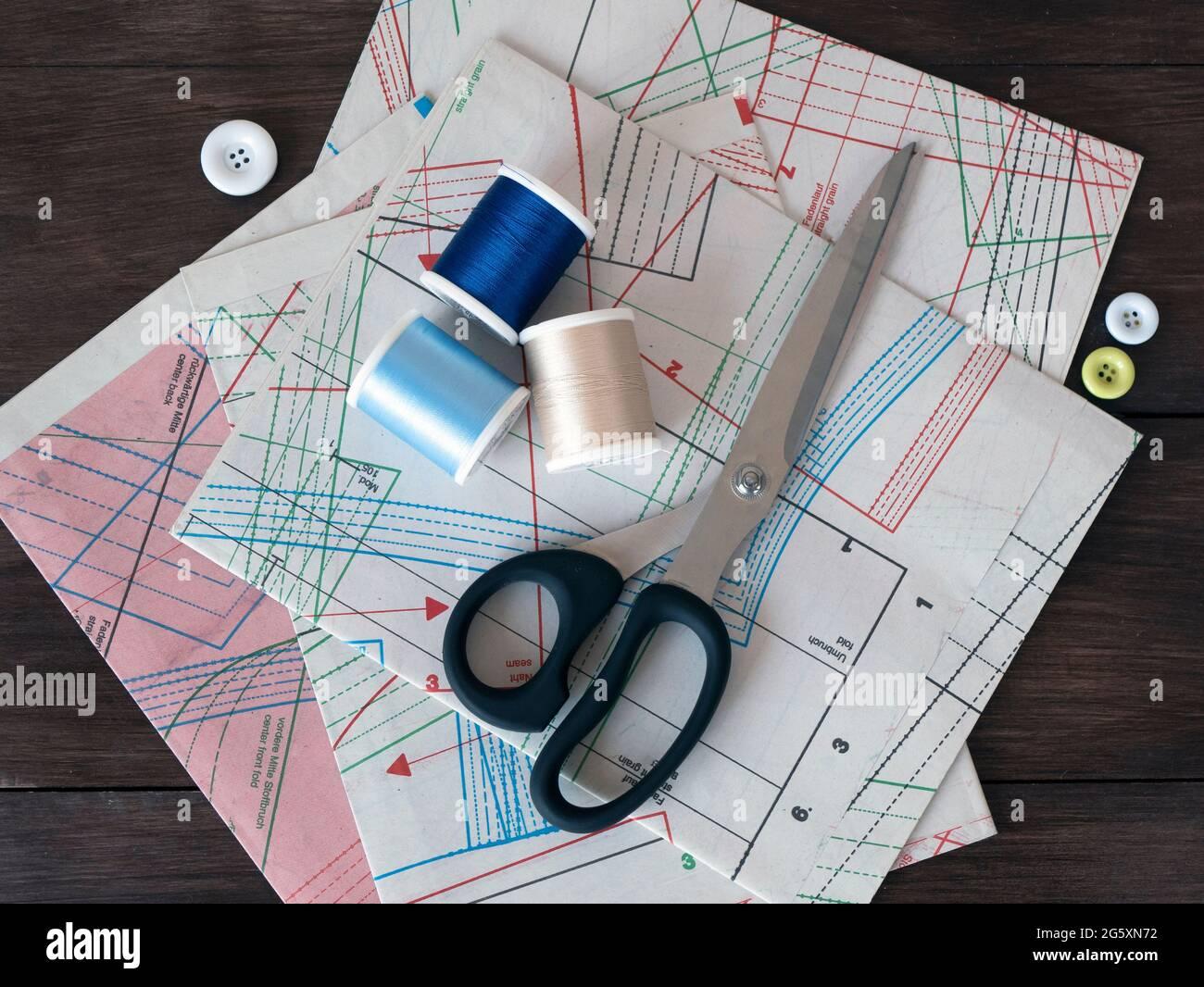 Hojas de dibujo para coser, tijeras de vendaje, carretes y botones sobre un fondo de madera oscura. Patrones de ropa profesional y artículos de costura Foto de stock