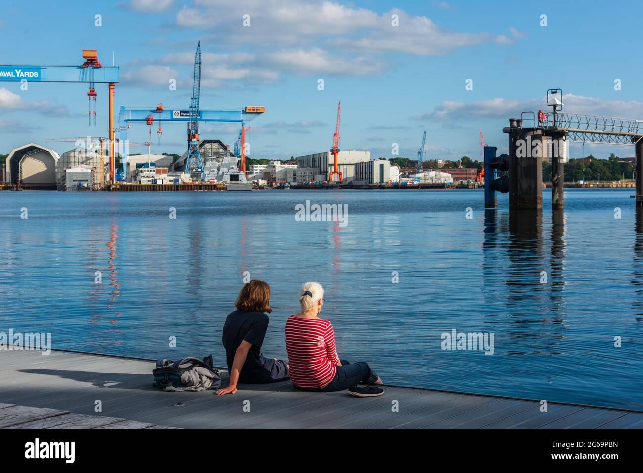 Zwei Frauen auf dem Anleger eines Kieler Ruderclubs an der Kiellinie an einem sommerlichen Abend Foto de stock