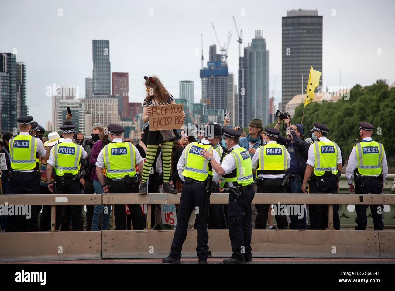 Un joven manifestante con orejas de gato y gafas amarillas sostiene un letrero en medio de la policía en la protesta 'Kill the Bill' en el centro de Londres, 5.7.2021 Foto de stock