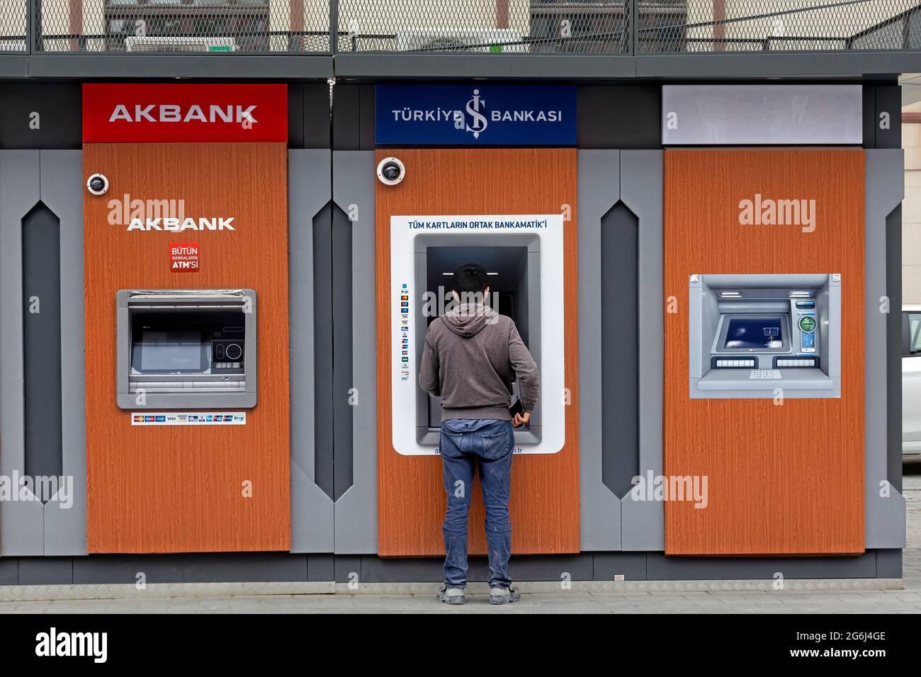 Hombre con vestido casual delante de Akbank, banco Isbank ATM s, retirada de dinero. Karakoy, Estambul - Turquía. Foto de stock