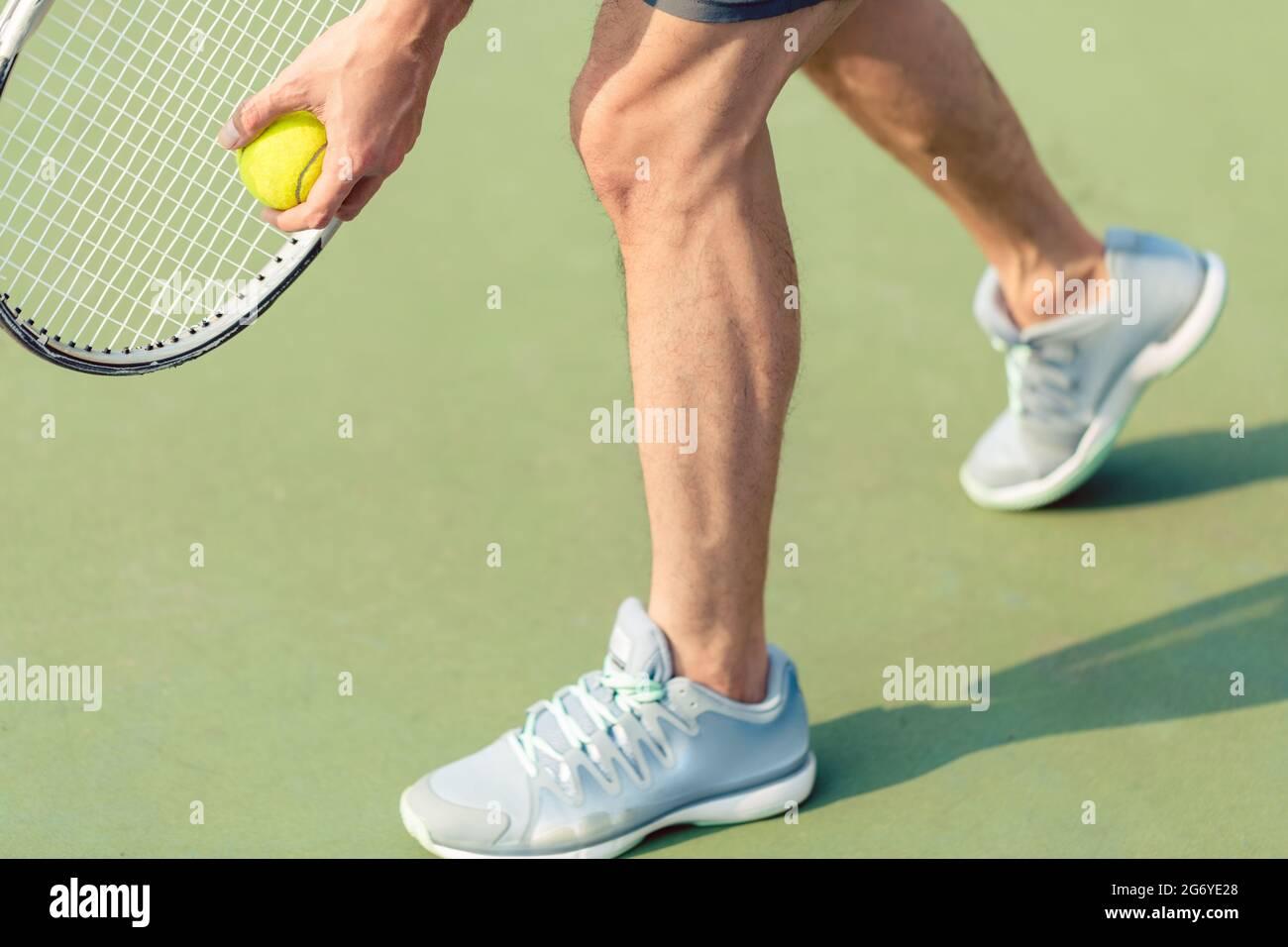 Sección baja de un jugador profesional que lleva calzado deportivo gris mientras sujeta la pelota y la raqueta de tenis durante el partido sobre una superficie verde Foto de stock