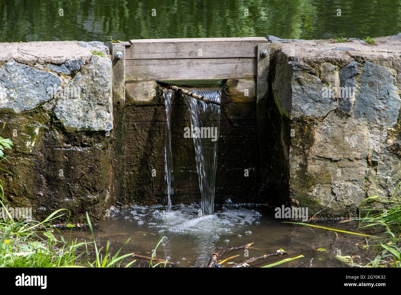 Un agua fluye a través de las esclusas en la pequeña presa de piedra del estanque Foto de stock