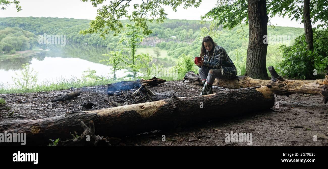 Una chica atractiva con una taza en su mano se sienta en un tronco y se calienta cerca de un fuego en el bosque. Foto de stock
