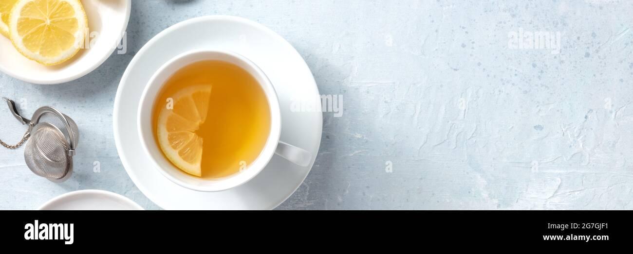 Panorama de té de limón con espacio de copia. Una taza de té con una rodaja de limón fresco, rodada desde la parte superior sobre un fondo de pizarra Foto de stock