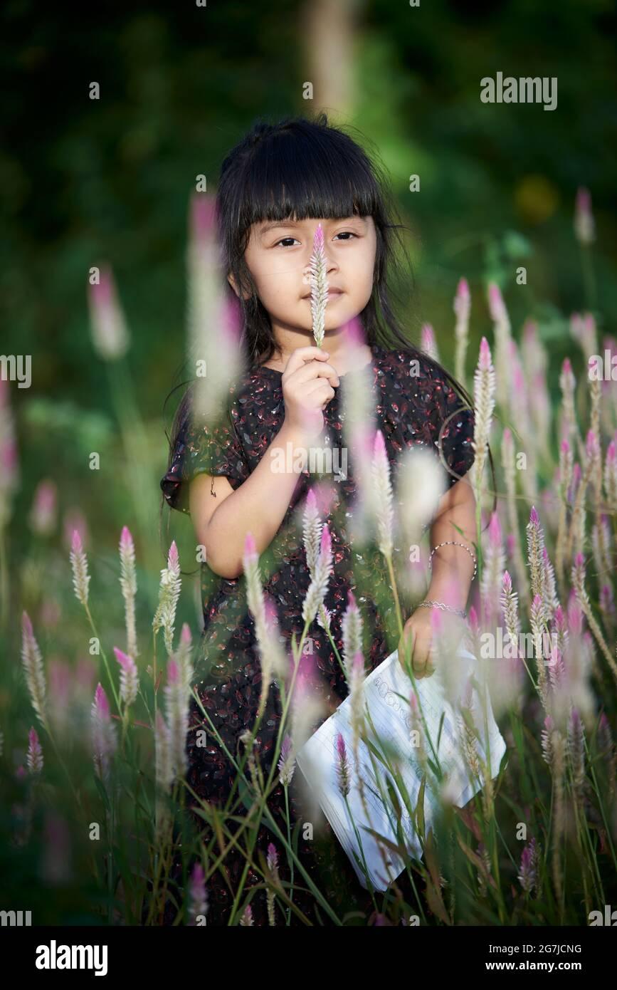 Linda niña disfrutando de la floración de flores silvestres en el campo de la pradera Foto de stock