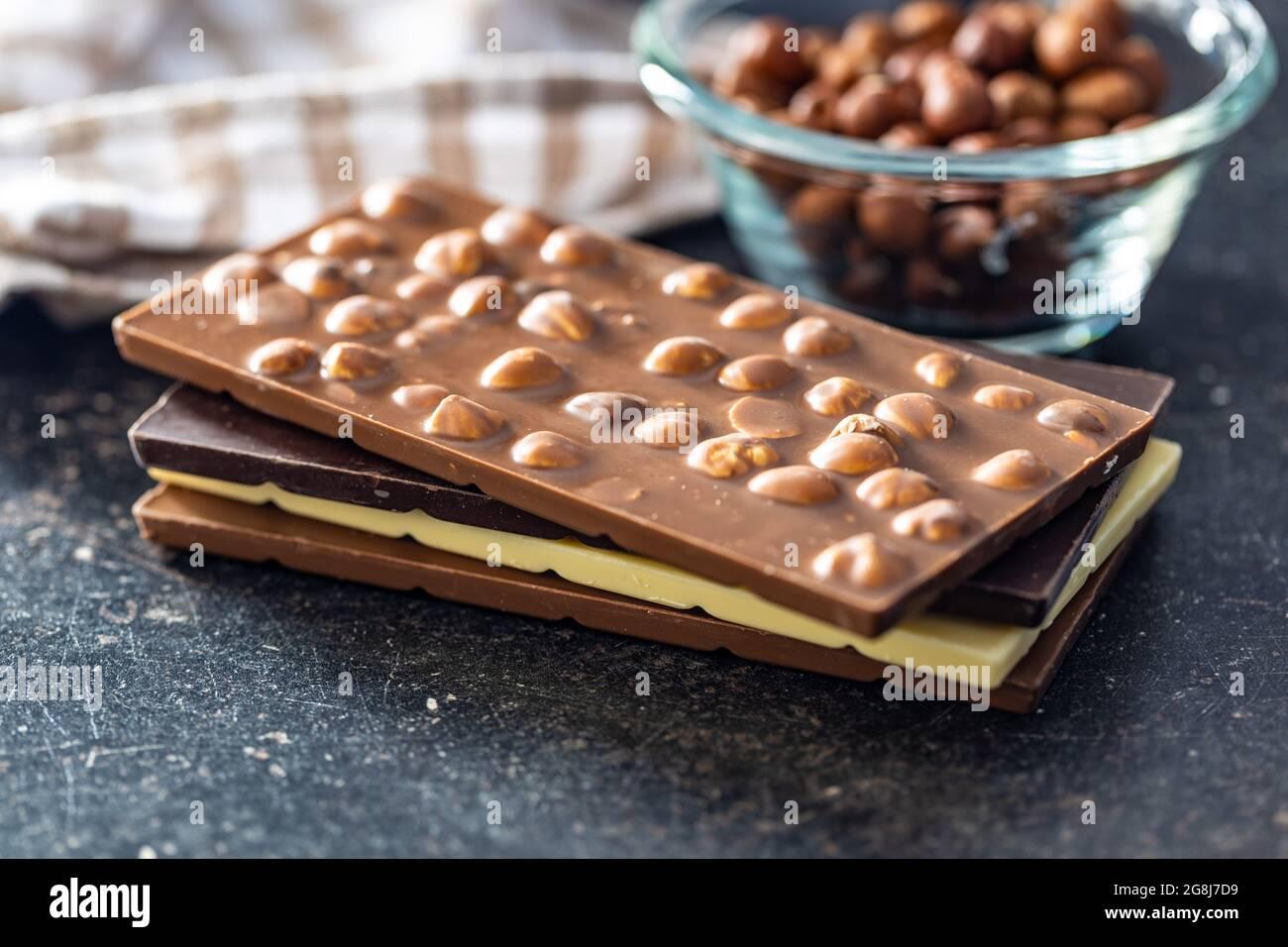 Varias barras de chocolate con avellanas sobre mesa negra. Foto de stock