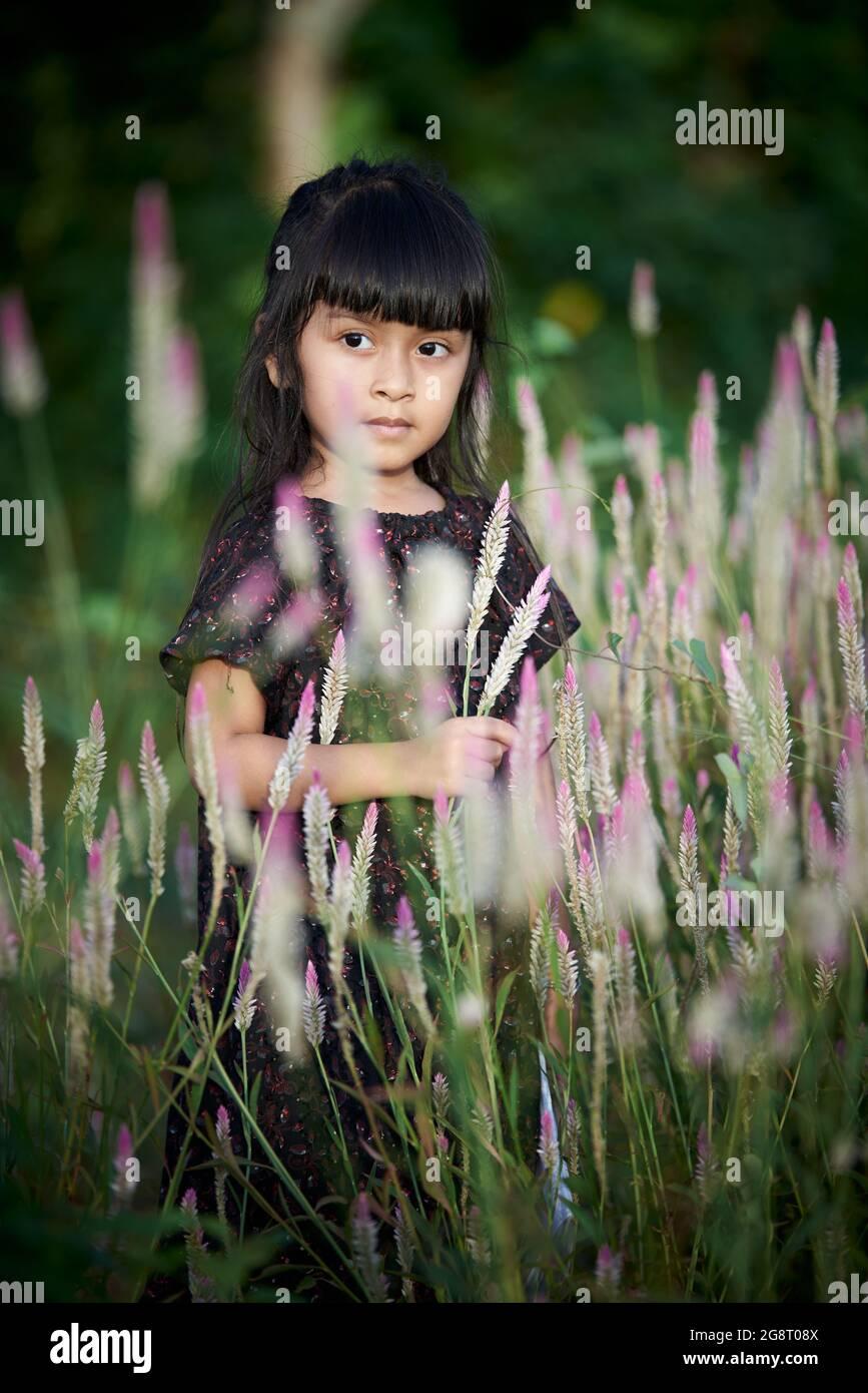 niña asiática jugando con flores silvestres en el jardín público Foto de stock