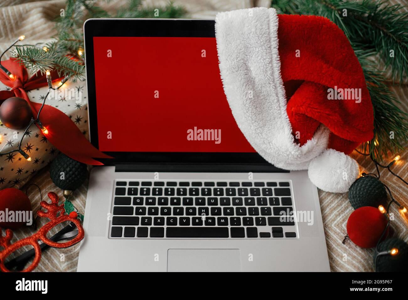Ventas de Navidad y compras en línea. Portátil con pantalla roja vacía en sombrero de santa claus en una cómoda cama con elegantes adornos navideños, luz actual y festiva Foto de stock