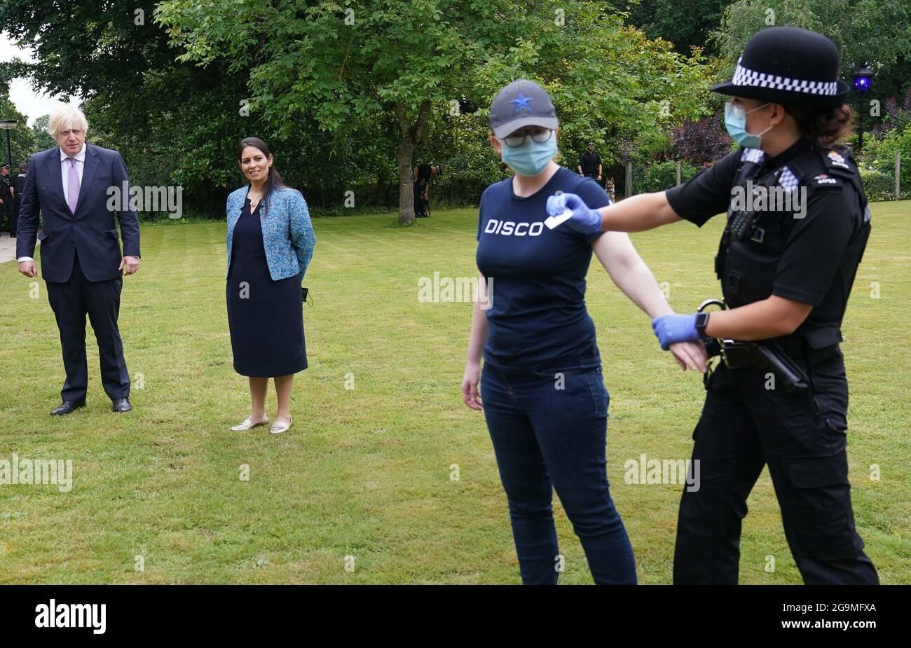 El Primer Ministro Boris Johnson y el Secretario del Interior Priti Patel observan un ejercicio de búsqueda durante una visita a la sede de la Policía de Surrey en Guildford, Surrey, coincidiendo con la publicación del Plan de Crimen de Gata del Gobierno. Fecha de la foto: Martes 27 de julio de 2021. Foto de stock