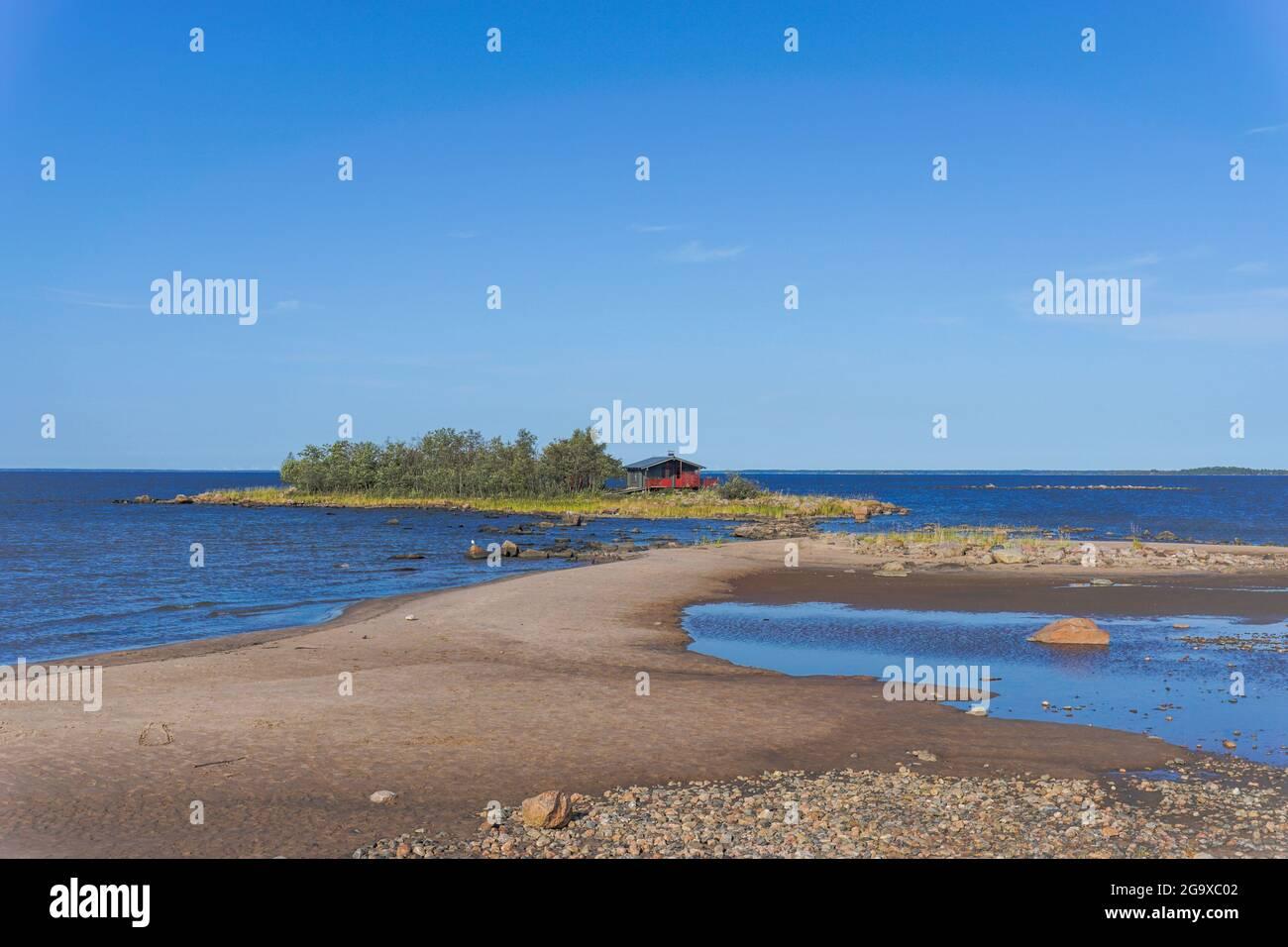 Un pintoresco paisaje costero en el Mar Báltico con una pequeña casa de campo roja en una isla detrás de una playa de arena bajo un cielo azul Foto de stock