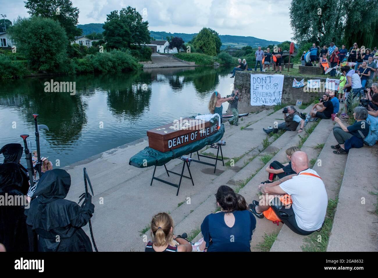 La especialista en natación salvaje y autora Angela Jones aka 'La Mujer Salvaje de la Wye' lleva un baño de 1km en la sección de Monmouth del río Wye para aumentar la conciencia sobre la condición ecológica terrible del río Wye y su continuo deterioro. Una réplica de ataúd en una tabla de paletas fue bajada al río y remolcada por Angela para representar la Muerte de la Wye. Su natación es parte de #SaveTheWye una campaña paraguas para apoyar y construir la red de organizaciones e individuos que trabajan para proteger y restaurar la salud del río Wye y sus afluentes, para beneficio tanto de la vida silvestre como de la gente Foto de stock