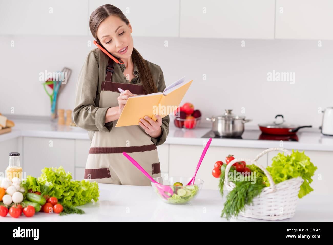 Foto de brillante dulce ama de casa vestido delantal marrón leer libro de cocina hablar moderno gadget interior habitación casa casa casa casa Foto de stock