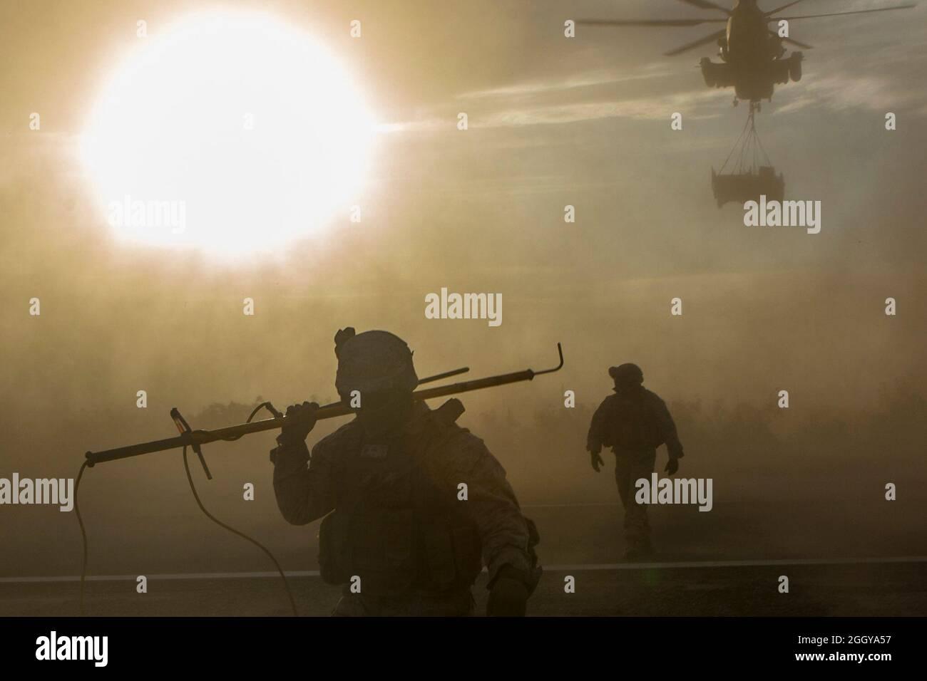 U.S. Marines, Lance Cpl. Sebastiane Megariz, a la izquierda, y Gunnery Sgt. Jeffery Addison Jr., derecha, ambos especialistas de apoyo de aterrizaje, con Combat Logistics Batallón 13, Combat Logistics Regiment 17, 1st Marine Logistics Group, reagruparse después de aparejos de vehículos tácticos en un Super Stallion CH-53E, asignado al Escuadrón de Armas y Tácticas de Aviación Marina (MAWTS-1), Durante un levantamiento directo del centro de apoyo aéreo en una base expedicionaria avanzada, en apoyo del curso de Instructor de Armas y Tácticas (WTI) 2-21, en el Auxiliar Airfield IV, cerca de Yuma, Arizona, 29 de marzo de 2021. WTI es un evento de entrenamiento de siete semanas Foto de stock