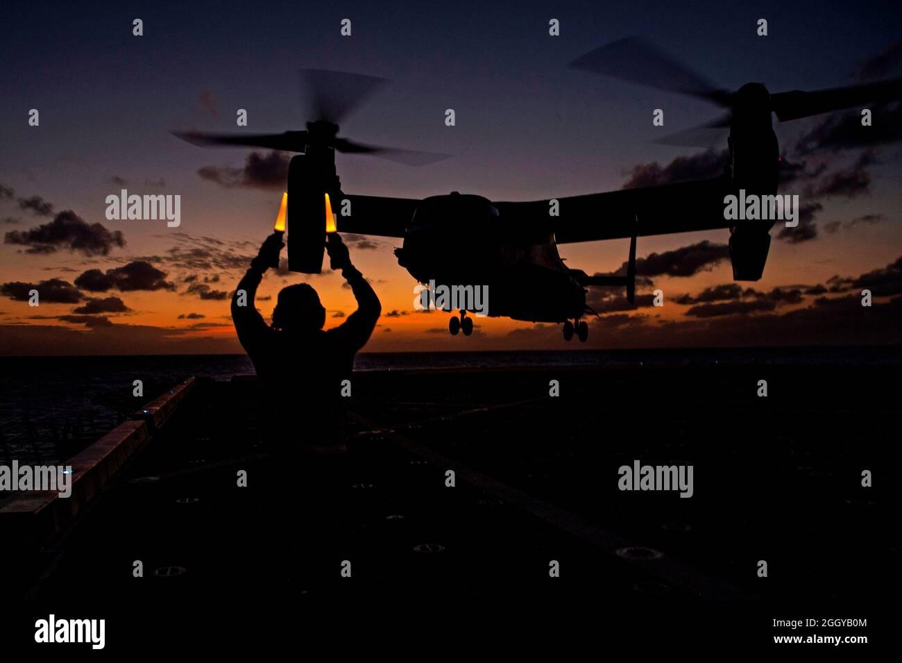 MAR FILIPINAS (18 de marzo de 2020) – Aviation Boatswain's Mate (Handling) 3rd Class Deon Sanders, del Bronx, N.Y., asignado al buque de transporte anfibio USS Green Bay (LPD 20), clase San Antonio, señala a un MV-22 Osprey asignado al buque de asalto anfibio USS America (LHA 6) cuando se despida de la cubierta de vuelo. Green Bay, parte del equipo de la Unidad Expedicionaria Marina del Grupo de Huelga Expedicionaria de América 31st, está operando en el área de operaciones de la Flota de Estados Unidos 7th para mejorar la interoperabilidad con aliados y socios y servir como una fuerza de respuesta lista para defender la paz y la estabilidad en la región del Indo-Pacífico Foto de stock