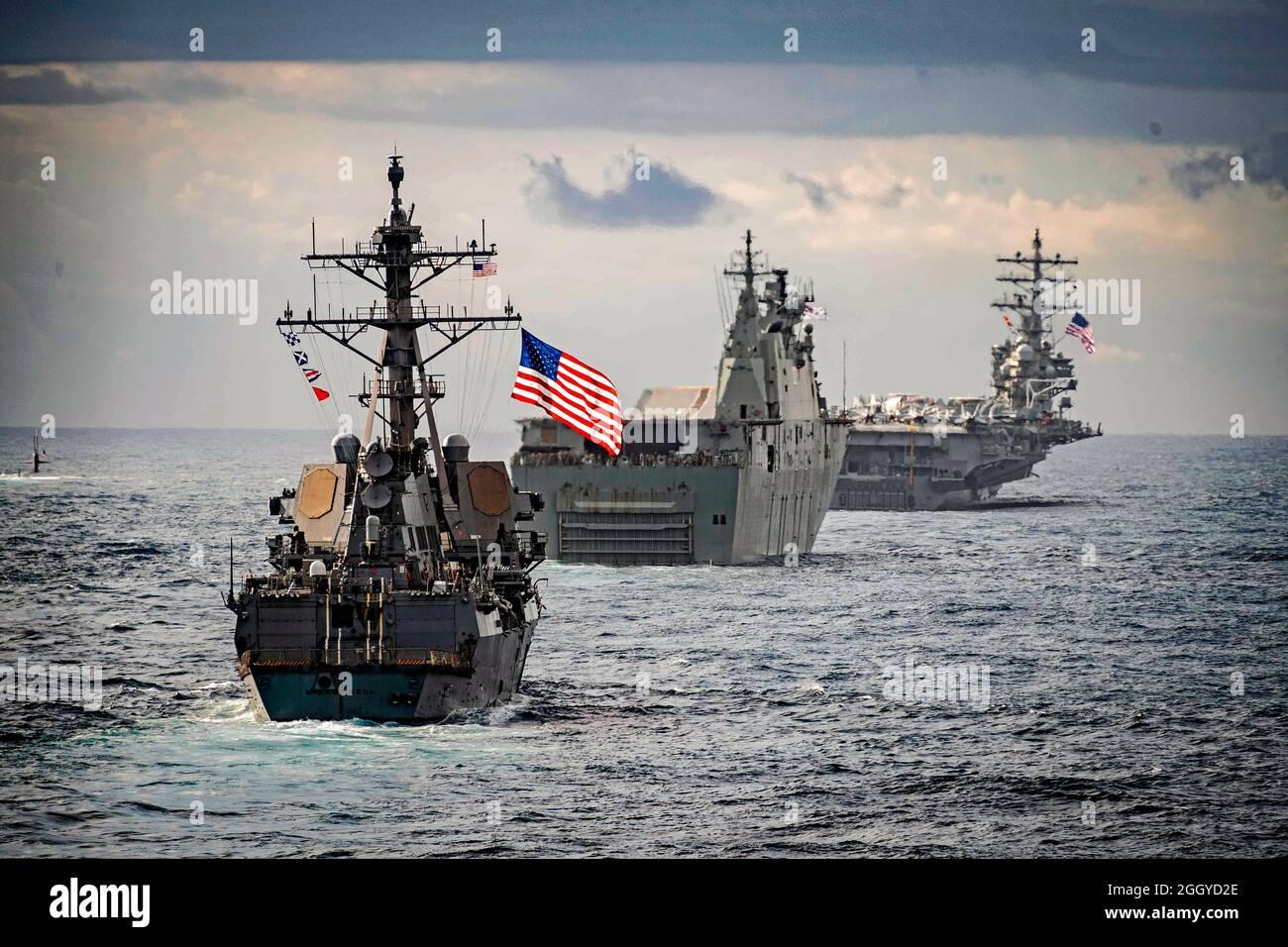 TASMAN SEA (11 de julio de 2019) El destructor de misiles guiados clase Arleigh Burke USS McCampbell (DDG 85), el muelle de helicópteros de aterrizaje clase Canberra de la Royal Australian Navy HMAS Canberra (L02), centro, el submarino de ataque clase Los Ángeles USS Key West (SSN 722), extremo izquierdo, Y el portaaviones de clase Nimitz USS Ronald Reagan (CVN 76) se está formando durante Talisman Sabre 2019. Ashland, que forma parte del grupo Wasp Anfibio Ready, con la Unidad Expedicionaria Marina 31st embarcada, participa actualmente en Talisman Sabre 2019 frente a la costa del norte de Australia. Un evento bilateral bienal, Foto de stock