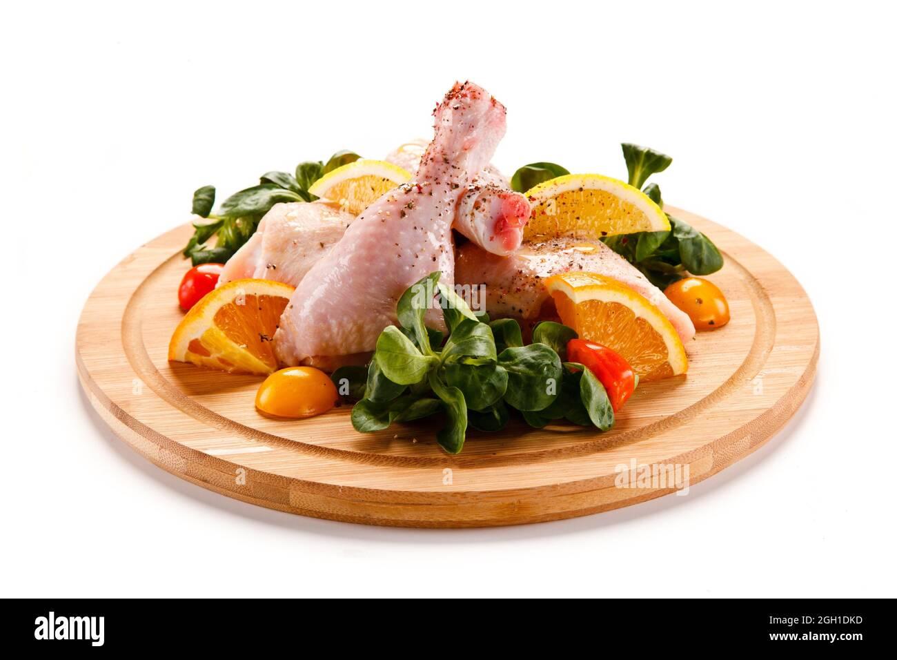 Chuletas de cerdo crudas en tabla de cortar y verduras. Foto de stock