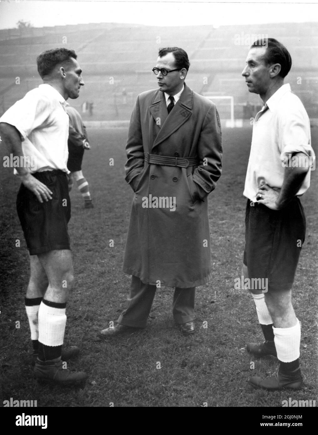Roy Bentley de Chelsea (izquierda) y Stanley Matthews de Blackpool en conversación con el gerente Walter Winterbottom en Charlton cuando los 17 jugadores de los cuales el equipo de Inglaterra para conocer Gales será elegido, informó para el entrenamiento . 1st de noviembre de 1954 Foto de stock
