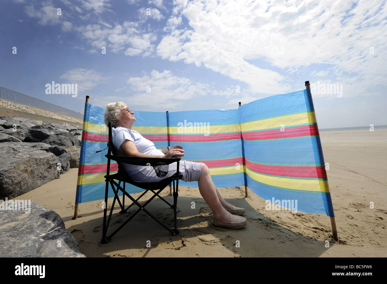 A  OLD AGE PENSIONER ENJOYS SUNBATHING ON A BRITISH BEACH WITH WINDBREAKER RE HOLIDAYS RETIREMENT OAPS PENSIONERS Foto de stock