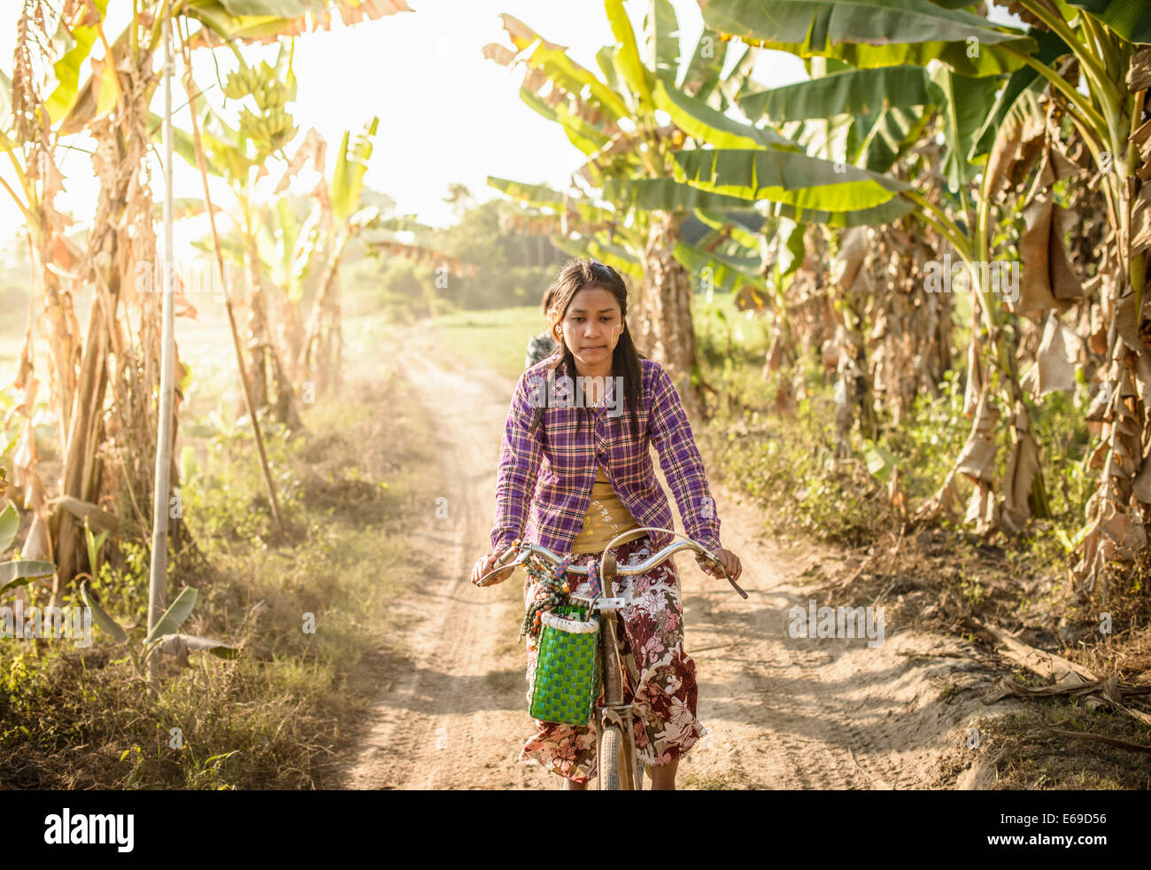 Asian woman riding bicycle on rural road Foto de stock