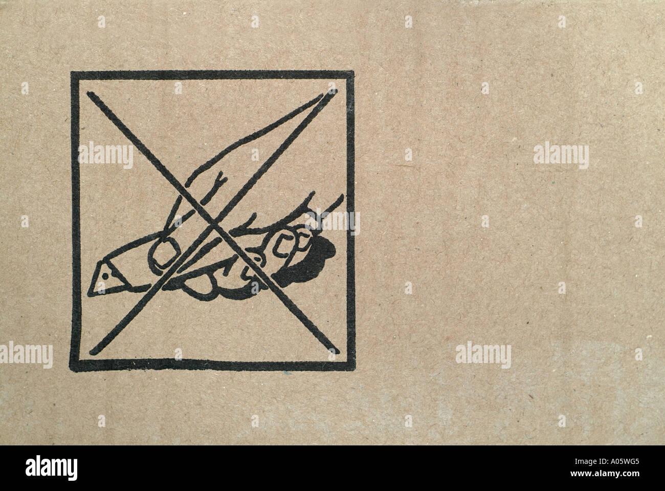 Símbolo de advertencia contra una caja de cartón con un cuchillo de apertura Imagen De Stock