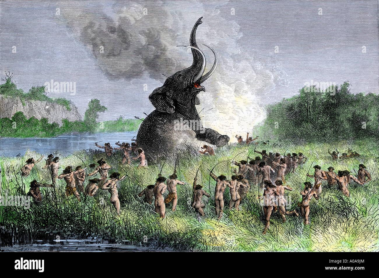 Wooly mammoth cazadores prehistóricos usando arcos y flechas. Xilografía coloreada a mano Foto de stock