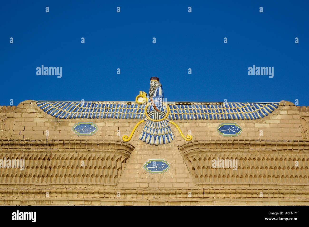 Una foto horizontal del símbolo alado de la religion Zoroastriana, encima de la entrada del templo de fuego de Yazd, Irán. Foto de stock