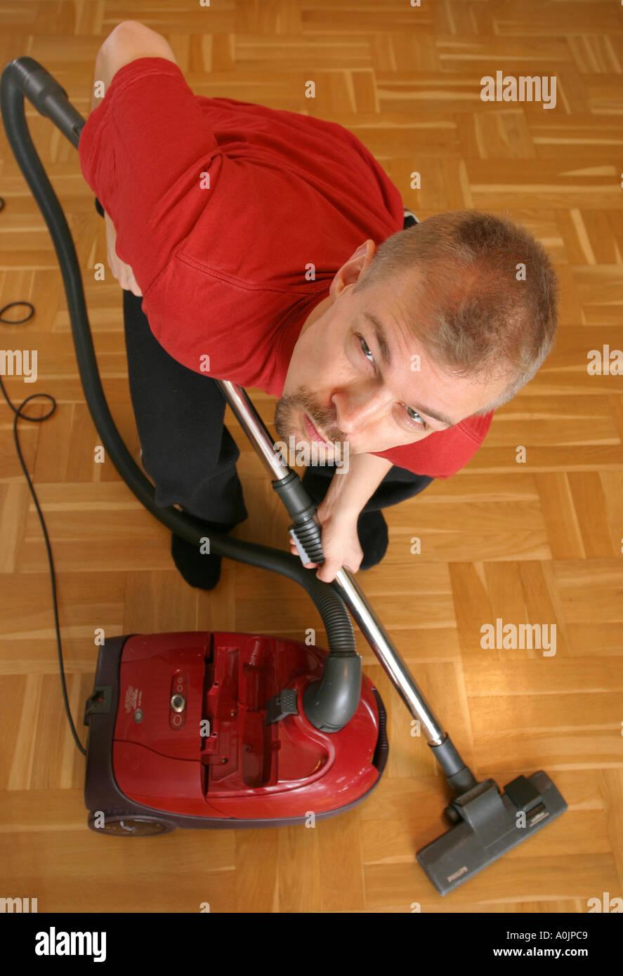 Gruñón hombre aspirando el suelo Foto de stock