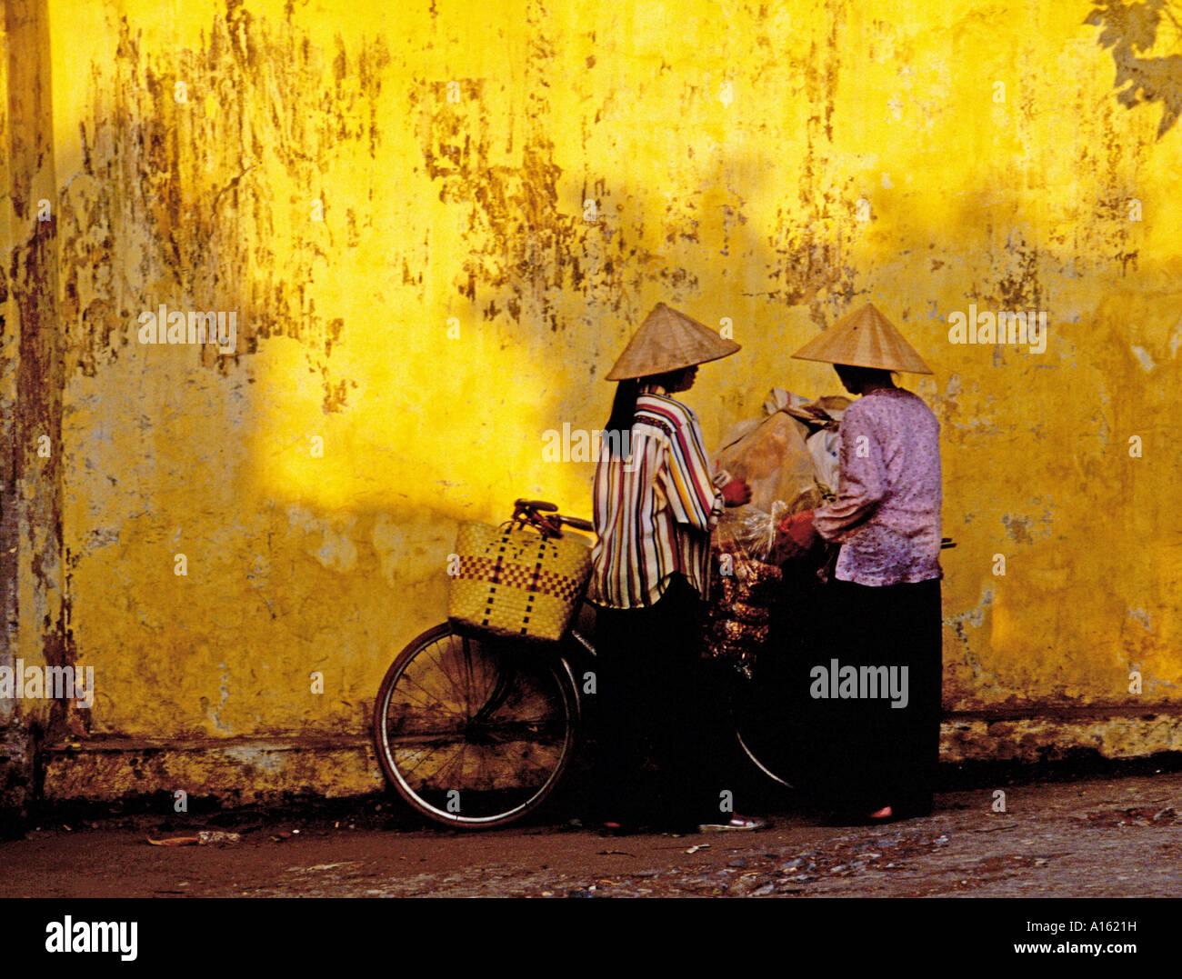 Dos mujeres con sombreros cónicos y bicicletas Hanoi, Vietnam. Foto de stock