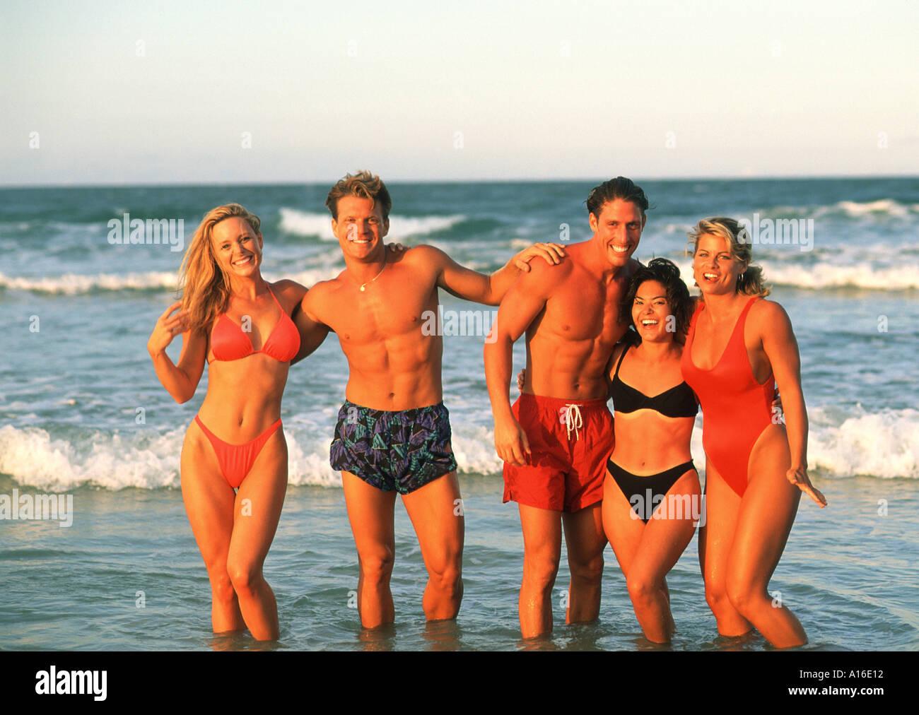 Los adolescentes atractivos de múltiples etnias divirtiéndose en la playa. Imagen De Stock
