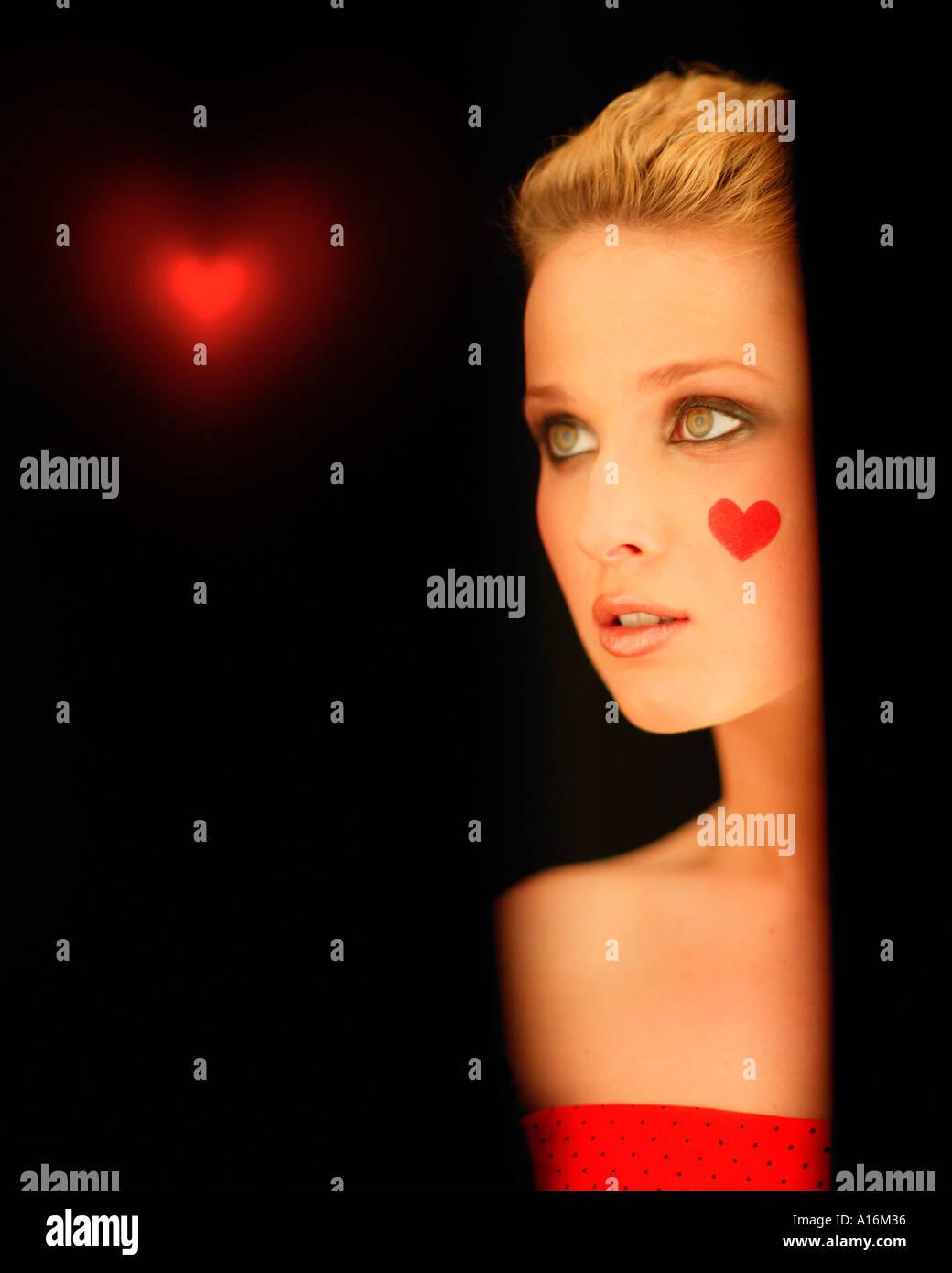 Retrato de una joven de 18, 19, 20-24, 24-29, 30-34, años con corazón rojo pintado en su mejilla Foto de stock