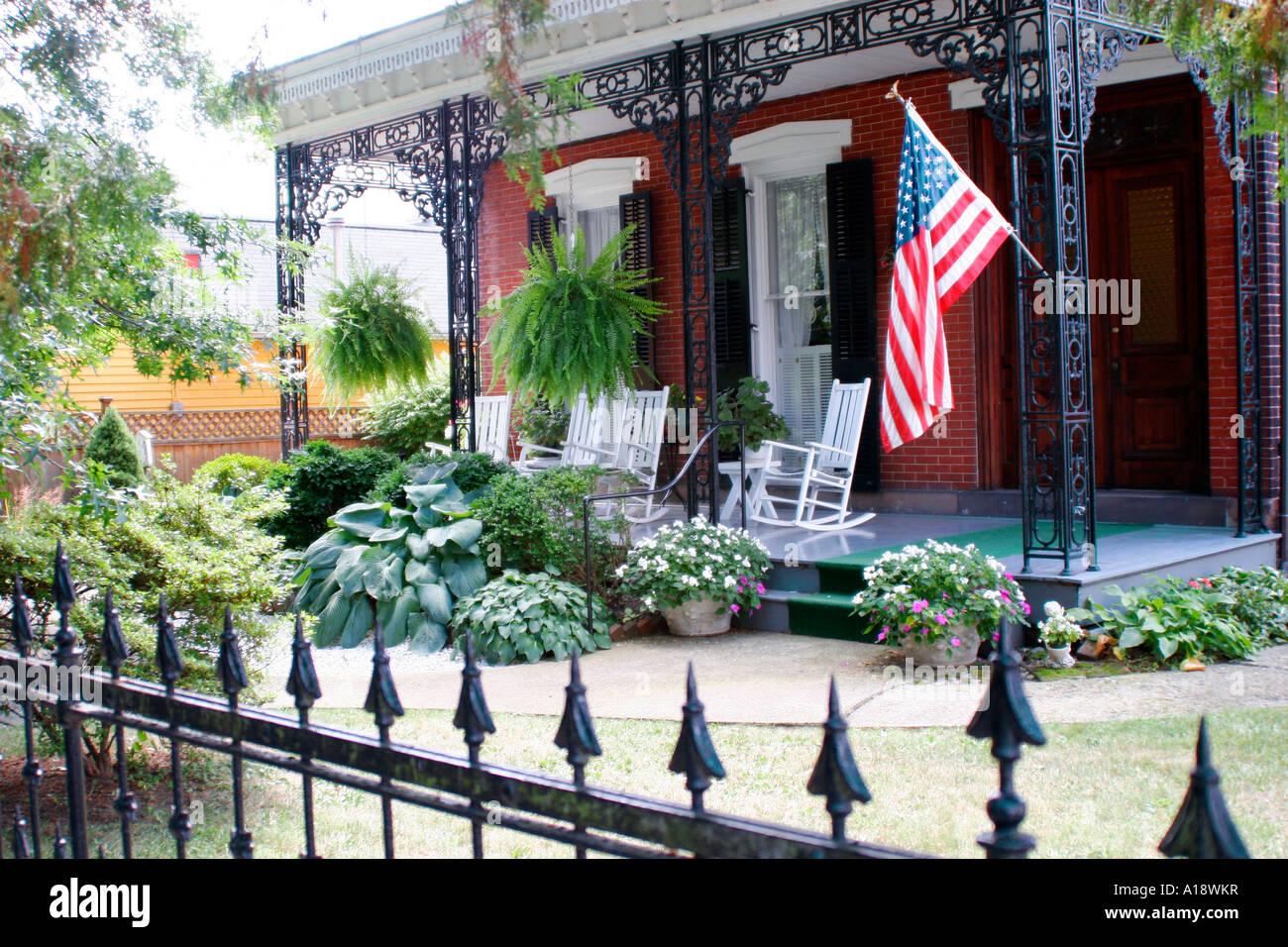 Casa colonial con cercas de hierro forjado y la bandera americana ...