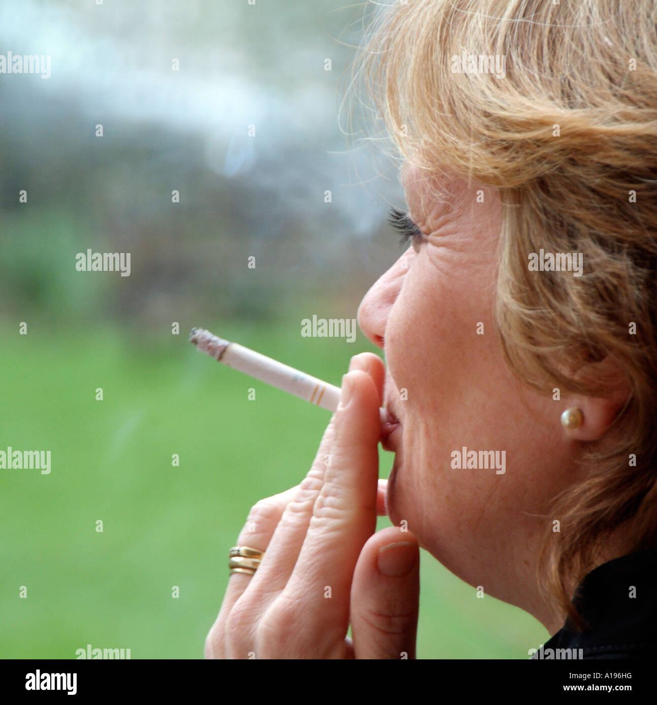 https://c1.alamy.com/compes/a196hg/mujer-fumando-un-cigarrillo-exhalando-humo-de-tabaco-a196hg.jpg