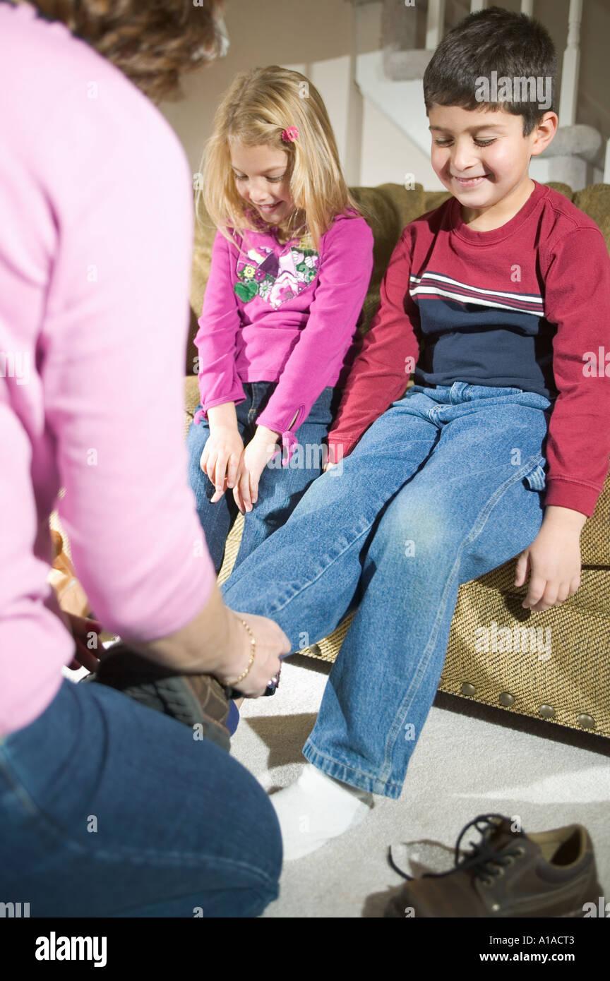 Madre poniendo en zapatos para niños. Foto de stock