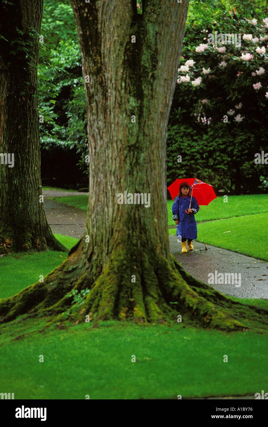 Una niña de siete años camina bajo su paraguas durante un resorte ducha en Seattle Washington Imagen De Stock
