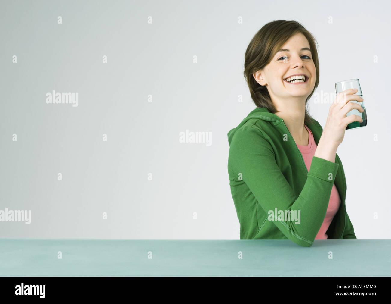Mujer joven sosteniendo el vidrio, sonriendo Imagen De Stock