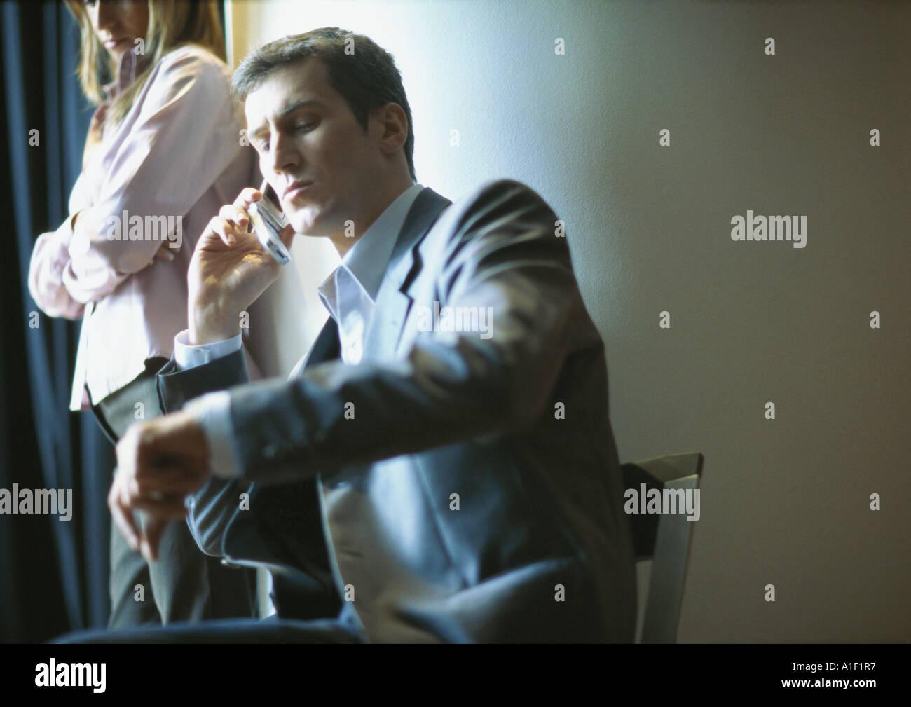 Empresario en el teléfono, el tiempo de revisión, mujer de pie junto a él Foto de stock