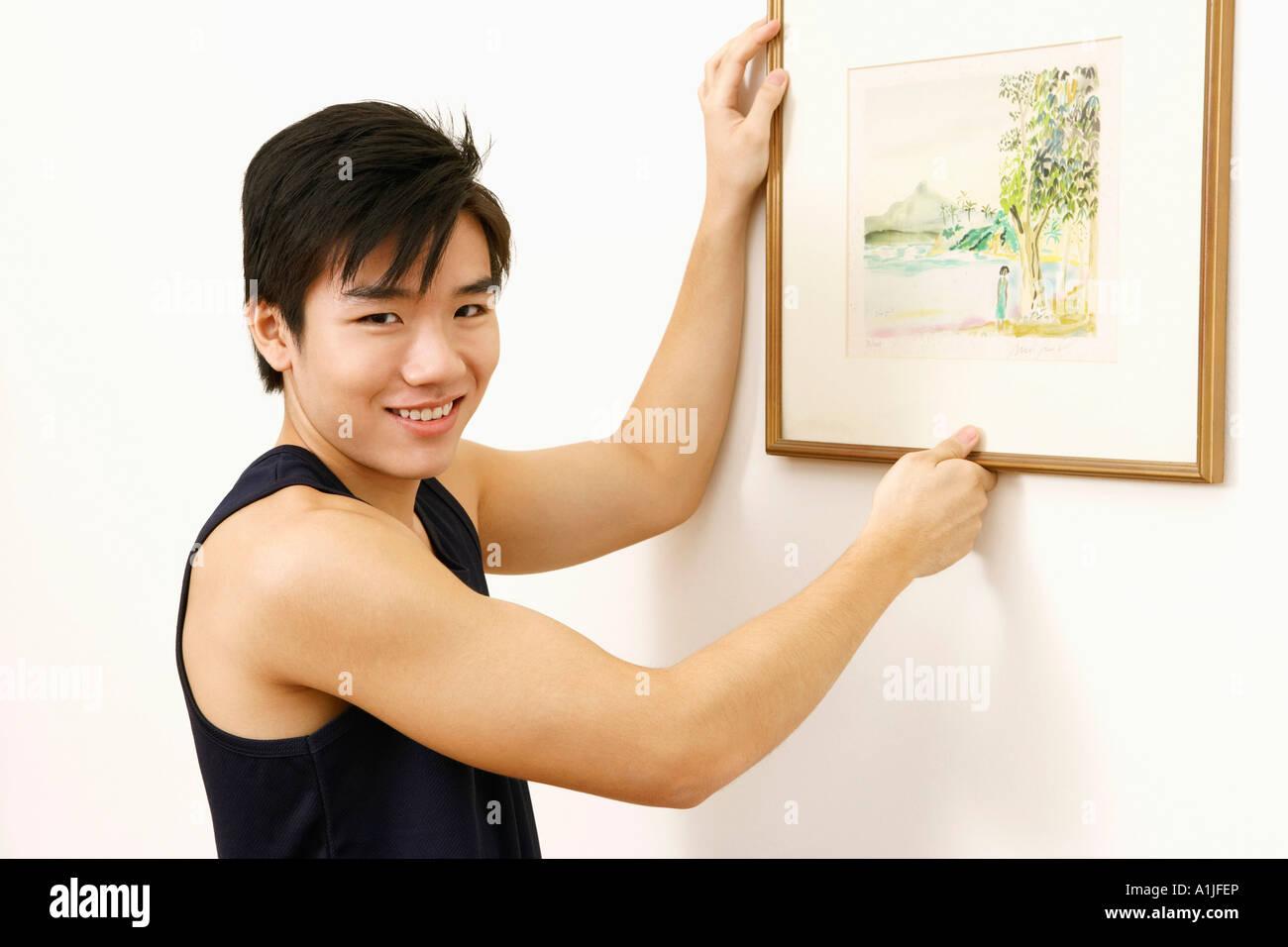 Retrato de un joven colgar un cuadro en la pared y sonriente Foto ...