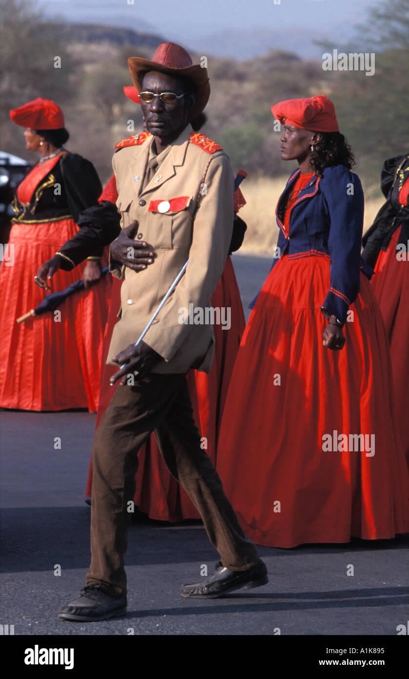 Estilo paramilitar soldado uniformado marchando junto a mujeres Herero para la Ma Herero del desfile del día de agosto de Okahandja Namibia Imagen De Stock