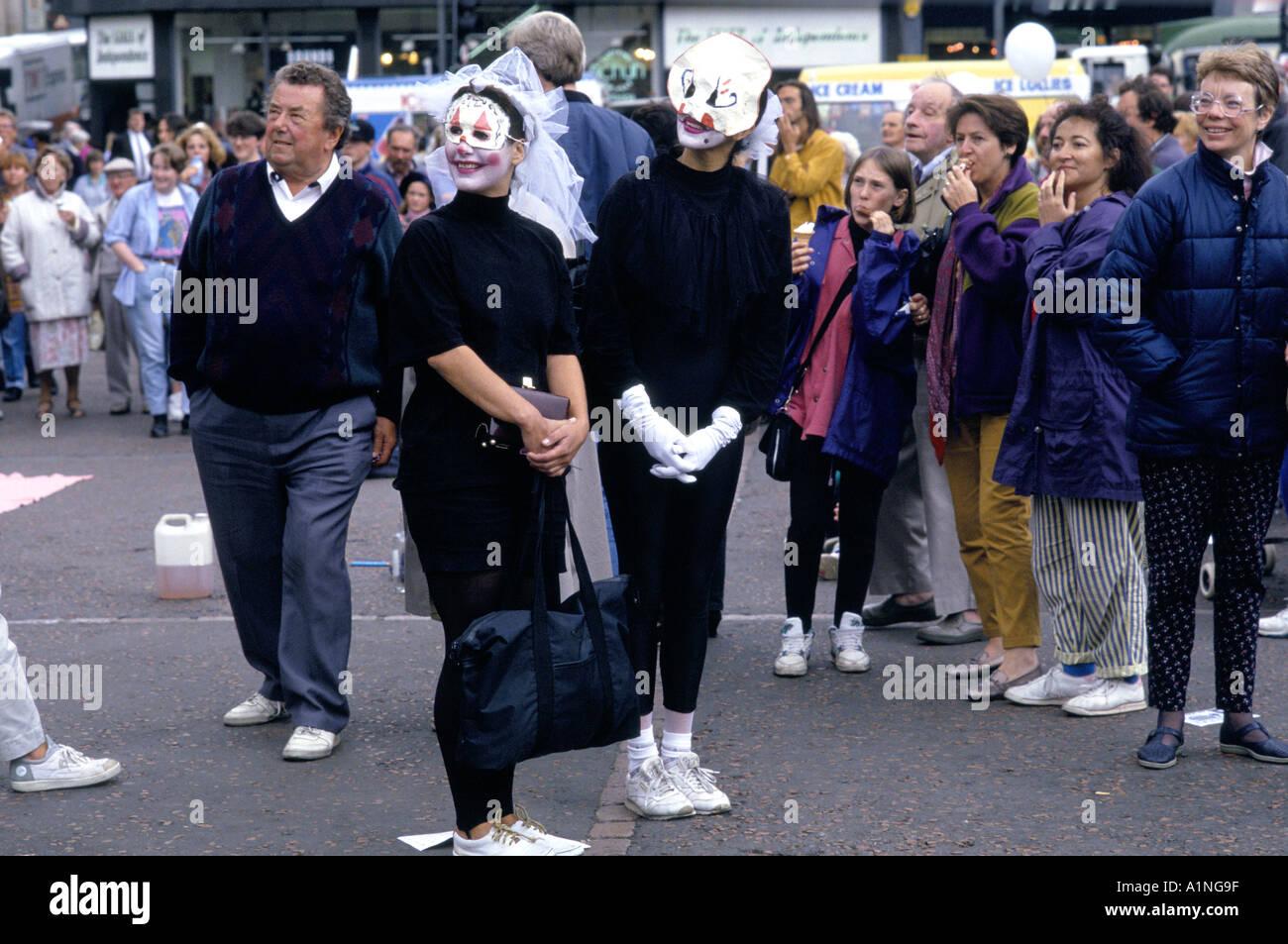 Los artistas intérpretes o ejecutantes en el B W disfraces máscaras oculares pintura facial EN UN ESPECTÁCULO DE CALLE transeúntes mirar en el Festival Fringe de Edimburgo Imagen De Stock