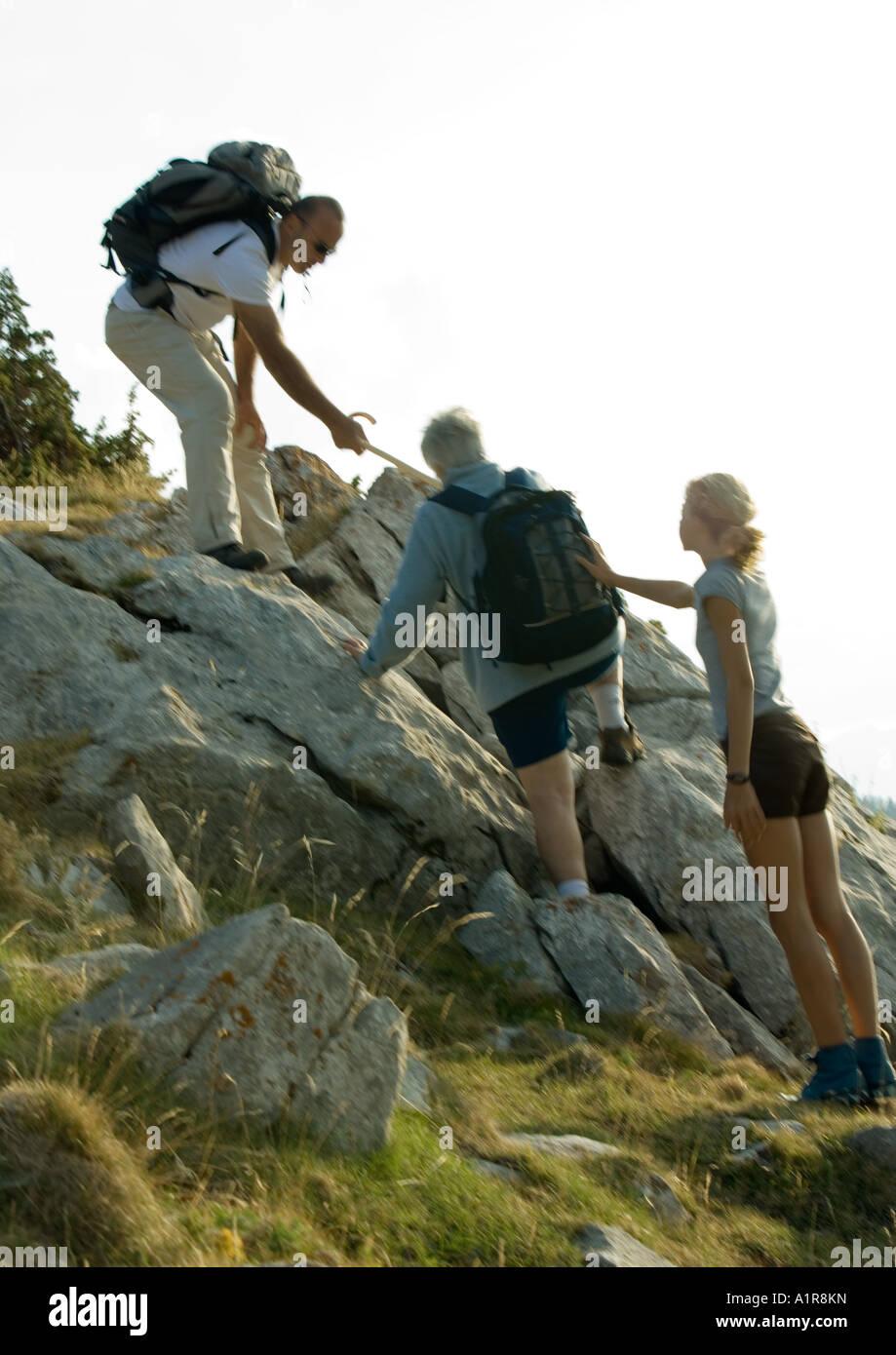 Excursionistas subiendo por las rocas, el hombre y la niña ayudando a mujer madura Foto de stock