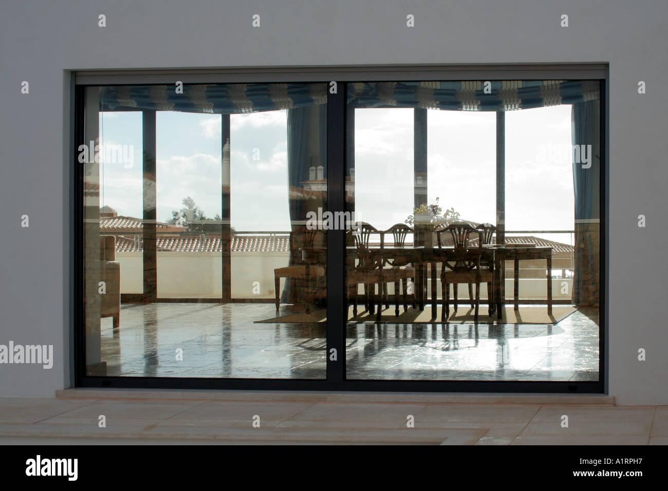 Ambiente casa modernista con miras comedor visto desde el exterior a través de la ventana la casa vecina reflejando Imagen De Stock