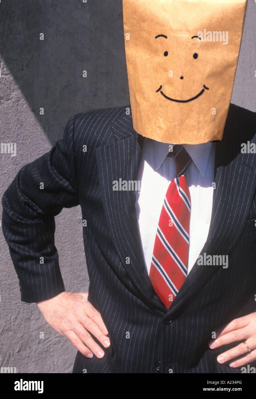 Empresario con bolsa de papel marrón sobre su cabeza sonriente Imagen De Stock