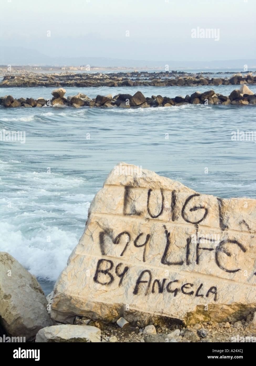 Amor murales sobre una roca, la playa de Villaggio Coppola, contaminación de Nápoles, Italia, campania Imagen De Stock