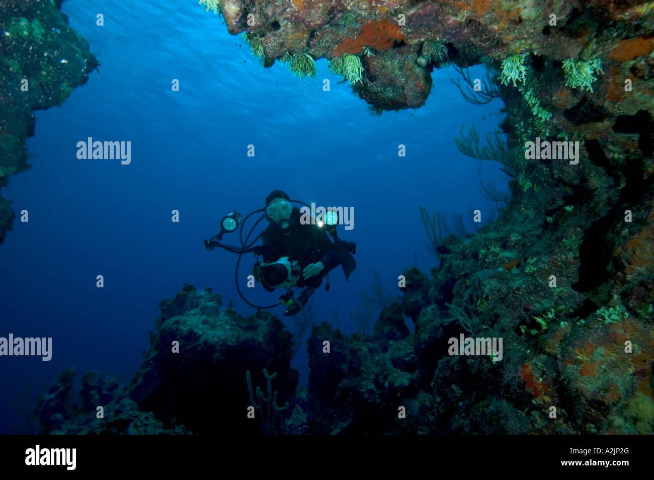 Una mujer fotógrafo mira hacia una caverna en un arrecife en Pequeño Caimán Foto de stock